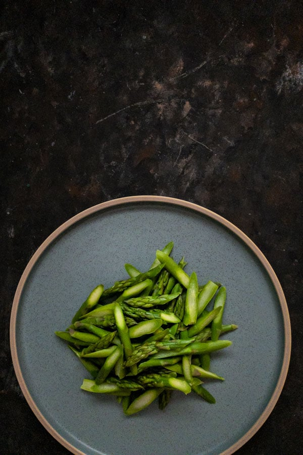 Sliced asparagus on a round blue plate