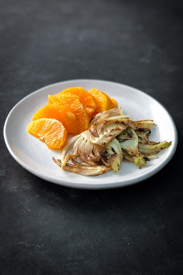 Orange slivers and charred fennel on white plate