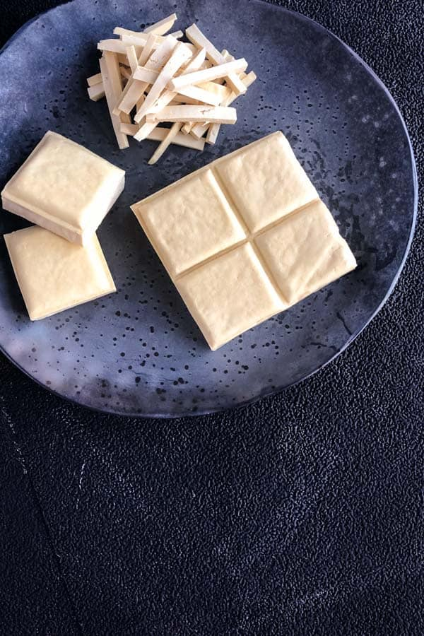 Square firm tofu and sliced on grey speckled plate