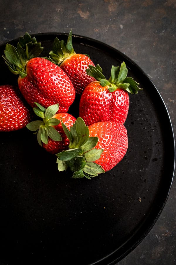 Strawberries on black plate for red fruit salad