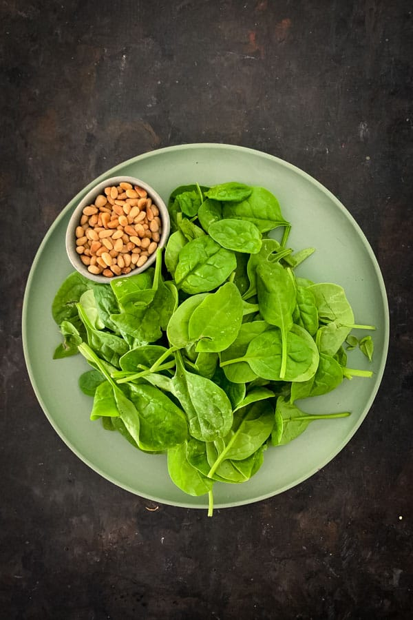 Toasted pine nuts and raw bay spinach