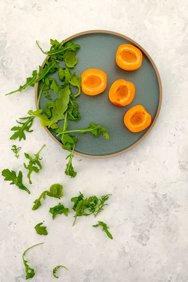 Halved apricots with arugula
