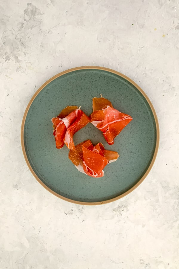Prosciutto Crudo on green plate