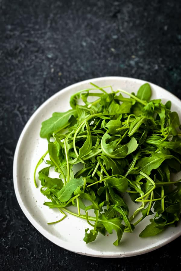 Rocket leaves or arugula leaves on a white plate