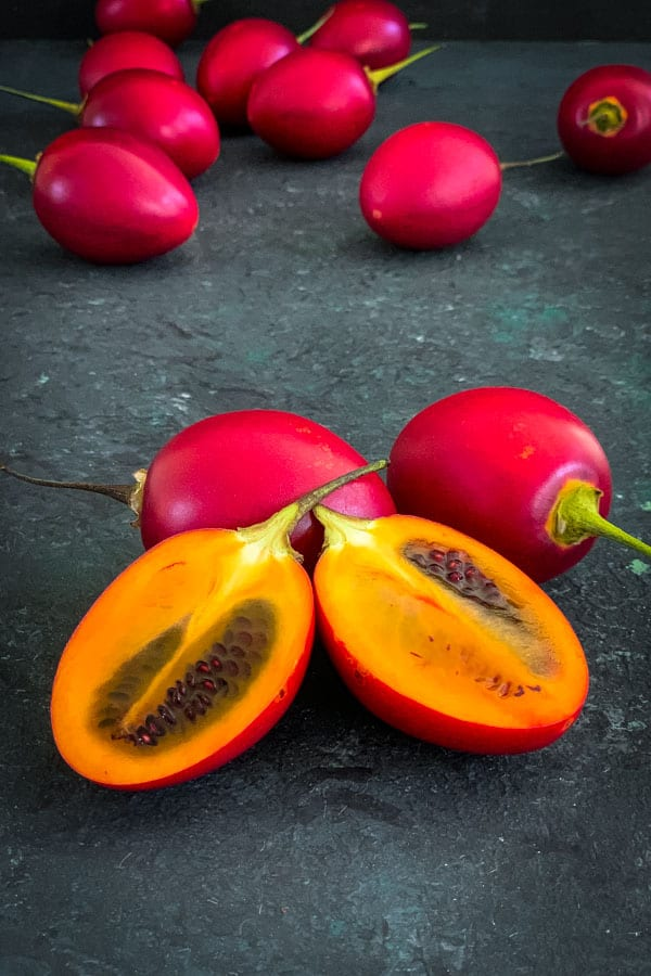 Whole red tamarillos and halves.