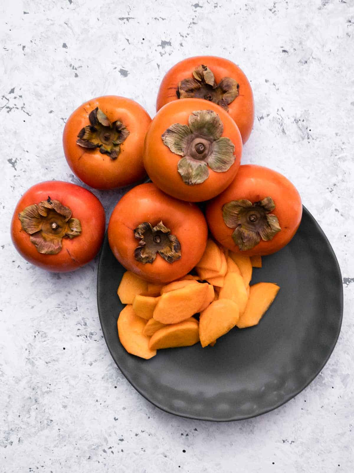 Whole and sliced persimmons